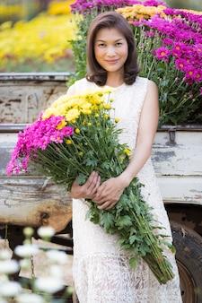 Portrait d'une belle femme asiatique tenant des fleurs jaunes dans les mains avec fierté, propriétaire de jardin fleuri satisfait de fleurs de bonne qualité à vendre.