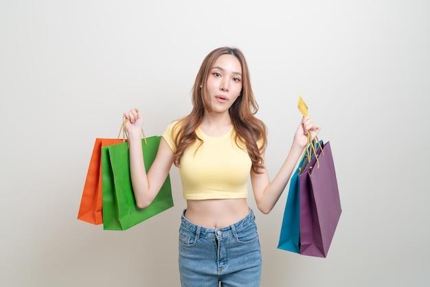 Portrait belle femme asiatique tenant un sac à provisions et une carte de crédit sur fond blanc
