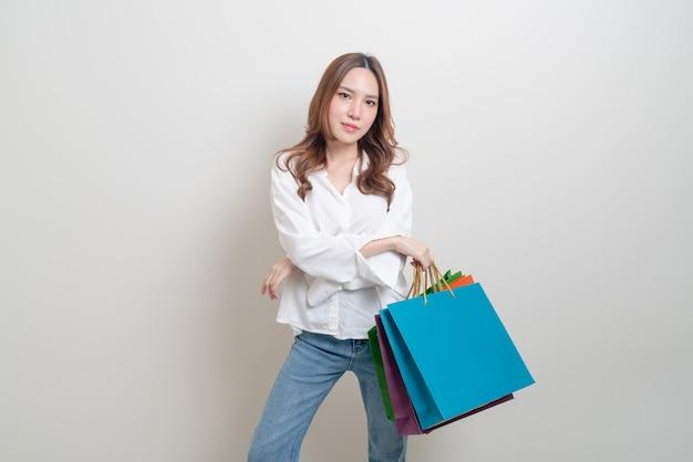 Portrait belle femme asiatique tenant un sac à provisions sur fond blanc