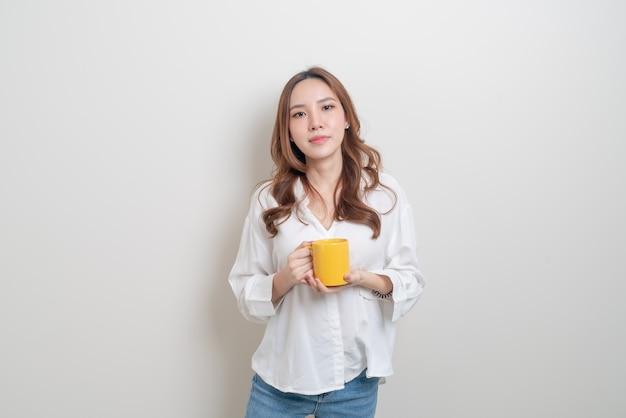 Portrait belle femme asiatique tenant une tasse de café ou une tasse sur fond blanc