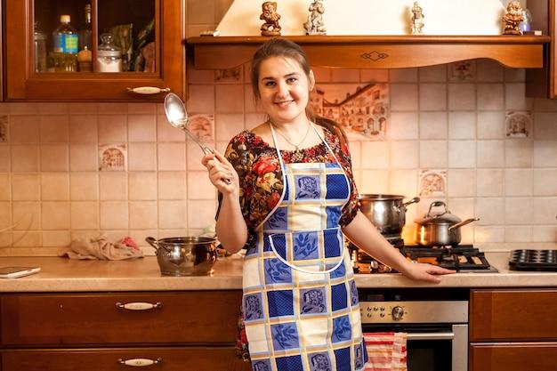 Portrait de belle femme au foyer tenant une louche sur la cuisine