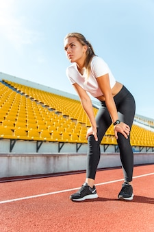 Portrait d'une belle femme au repos après avoir couru sur le stade