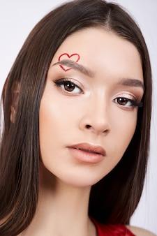 Portrait d'une belle femme aux cheveux bruns, maquillage professionnel, beaux yeux, cheveux longs et forts