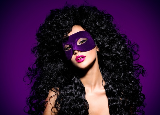 Portrait d'une belle femme aux cheveux noirs et masque de théâtre violet sur le visage. ongles violets.
