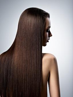 Portrait de la belle femme aux longs cheveux bruns tout droit au studio