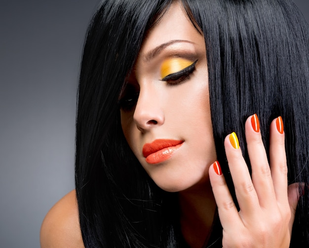 Portrait d'une belle femme aux ongles rouges et maquillage glamour et longs cheveux noirs