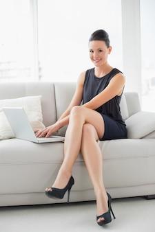 Portrait d'une belle femme bien habillée à l'aide d'ordinateur portable sur le canapé