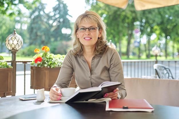 Portrait d'une belle femme blonde d'âge moyen réussie dans un restaurant en plein air d'été