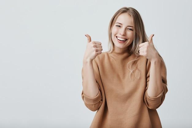 Portrait de belle femme blonde aux cheveux blonds avec un large sourire et les pouces vers le haut
