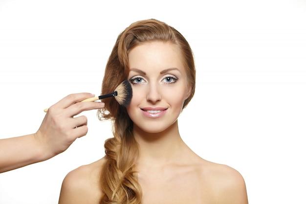 Portrait de la belle femme blonde aux cheveux longs et pinceau de maquillage près de visage attrayant