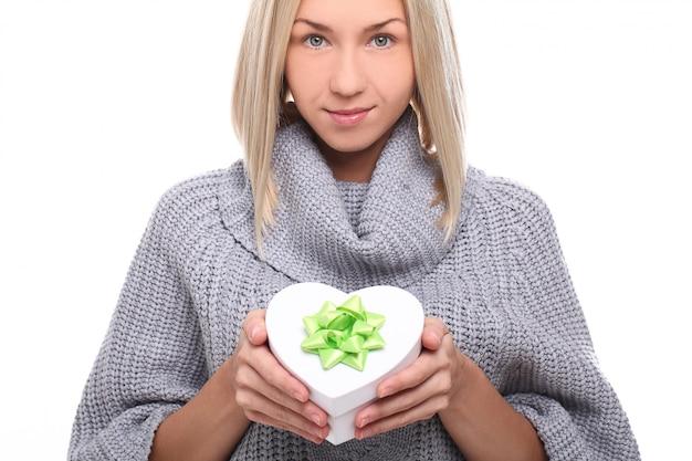 Portrait de la belle femme blonde avec boîte-cadeau en forme de coeur