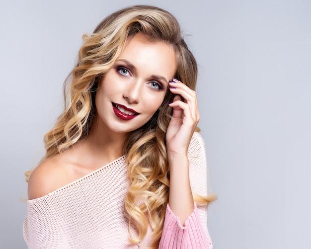 Portrait de belle femme blonde avec une coiffure frisée et maquillage lumineux.