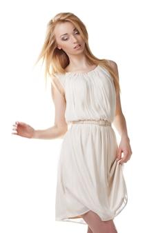 Portrait de belle femme blonde dansante aux cheveux longs sur fond blanc