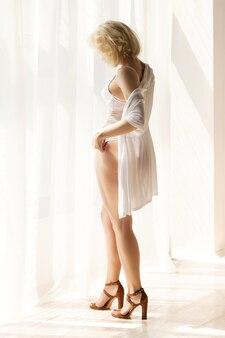 Portrait de la belle femme blonde debout près de la fenêtre et penser à quelque chose