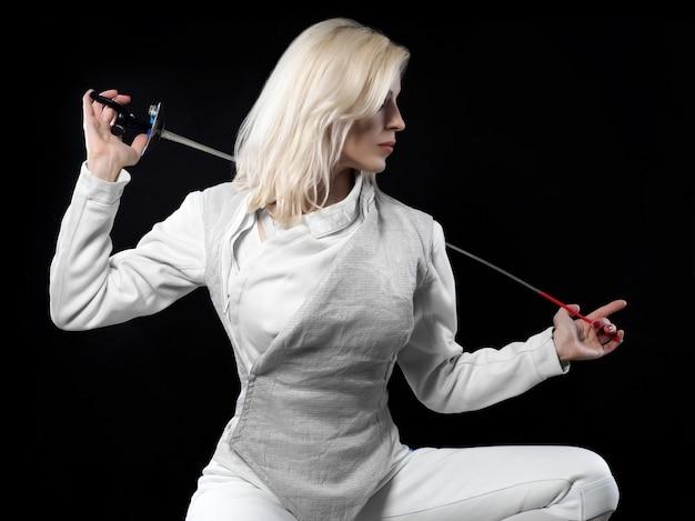 Portrait de belle femme blonde escrimeur tenant la rapière. sports olympiques, arts martiaux, protection et concept d'entraînement professionnel