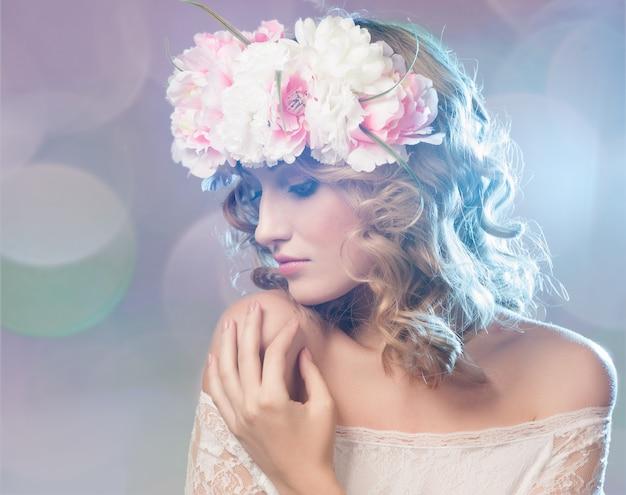 Portrait d'une belle femme blonde avec des fleurs dans les cheveux.