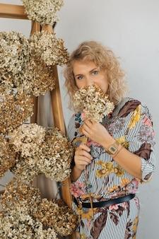 Portrait de belle femme blonde, fleurs sur son visage, fleuriste décorateur d'intérieur, souriant à la recherche dans le cadre. espace de copie. concept de décor d'automne naturel.