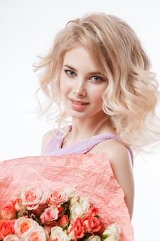 Portrait de la belle femme blonde frisée avec un maquillage parfait. tenant le bouquet.