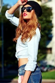 Portrait de la belle femme blonde hipster modèle en été décontracté élégant jeans bleu vêtements en lunettes de soleil posant dans la rue