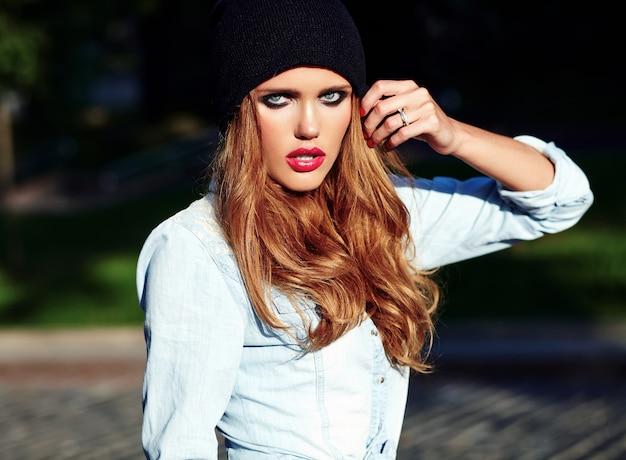 Portrait de la belle femme blonde hipster modèle en été décontracté élégant jeans bleu vêtements posant dans la rue