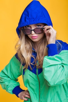 Portrait de belle femme blonde à lunettes de soleil et veste à capuche bleu vert sur fond jaune hi...