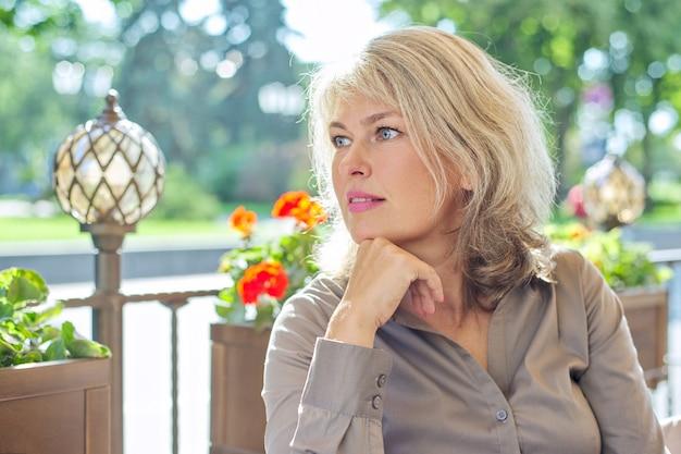 Portrait de belle femme blonde mature réussie dans le restaurant en plein air d'été, espace copie
