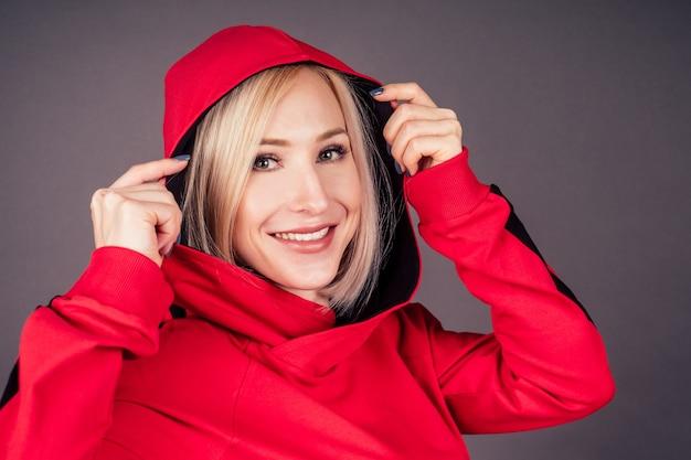 Portrait d'une belle femme blonde peau parfaite et maquillage mis sur capuche sweat à capuche survêtement rouge costume de sport danseur hip hop en studio sur fond noir. bob coiffure courte style sensuel