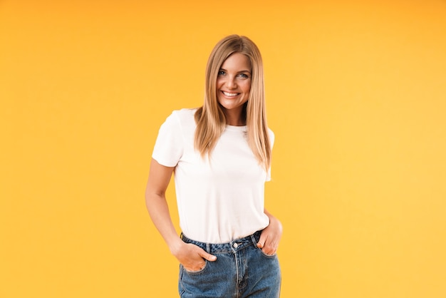 Portrait d'une belle femme blonde portant un t-shirt décontracté souriant à l'avant en se tenant debout avec les bras dans la poche isolé sur un mur jaune en studio