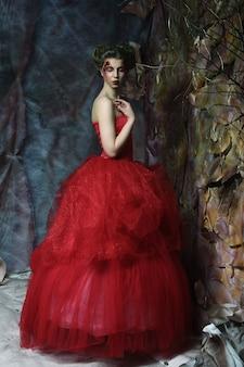 Portrait d'une belle femme blonde en robe rouge. maquillage et coiffure créatifs. tourné dans une maison fantastique.