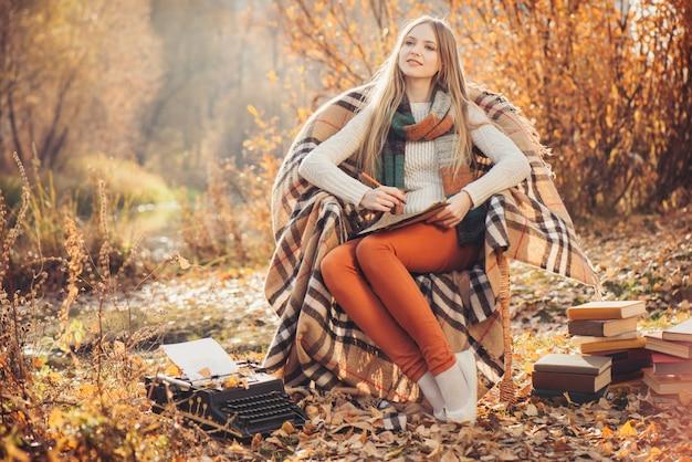 Portrait de la belle femme blonde en saison d'automne. écrivain femme dans le parc en automne