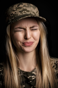 Portrait d'une belle femme blonde soldats en tenue militaire sur fond noir. émotion dégoût