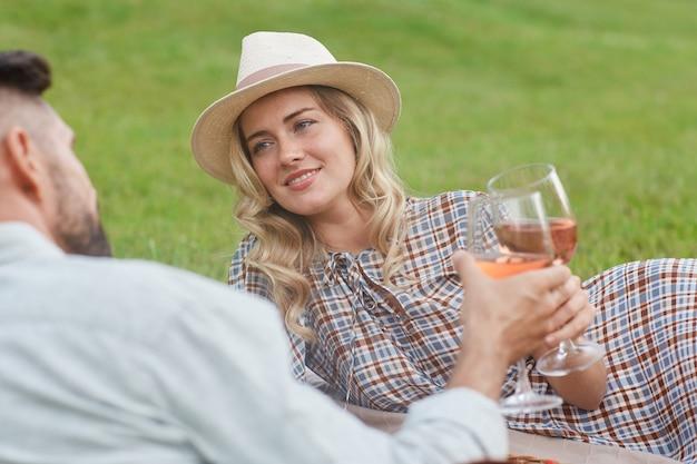 Portrait de la belle femme blonde tenant un verre à vin tout en profitant de pique-nique sur l'herbe verte pendant une date romantique en plein air