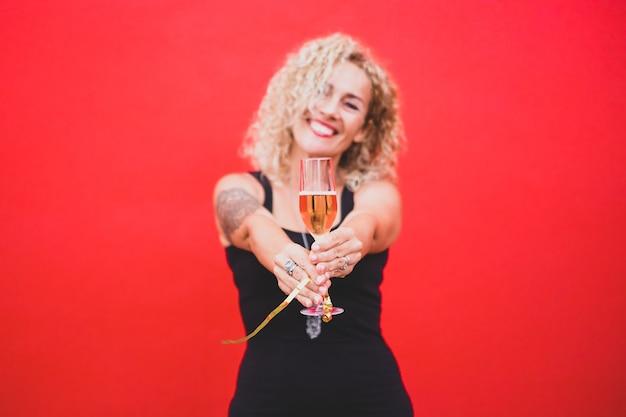 Portrait belle femme bouclée célébrant le nouvel an 2021 souriant et regardant la caméra tenant un verre ou une tasse de champagne