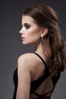 Portrait de belle femme avec boucles d'oreilles et robe noire