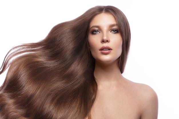 Portrait d'une belle femme brune aux cheveux parfaitement bouclés et au maquillage classique. visage et cheveux de beauté. photo prise en studio sur fond blanc.