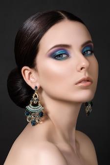 Portrait de la belle femme brune avec des boucles d'oreilles bleues