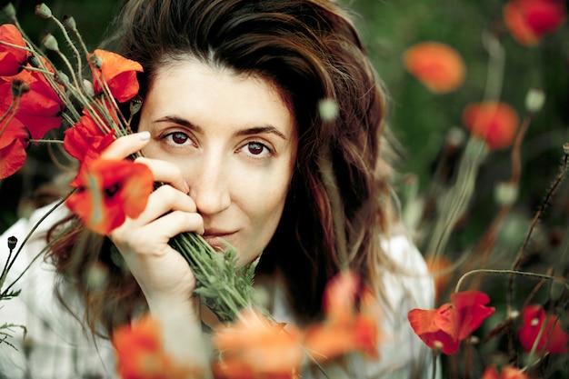 Portrait de la belle femme brune avec le bouquet de fleurs de coquelicots