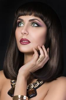 Portrait de la belle femme brune bronzée touchant son visage et portant une bijouterie d'or