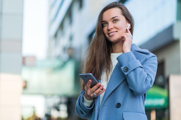Portrait de la belle femme brune joyeuse joyeuse élégante dans un manteau bleu avec un casque blanc sans fil dans le centre-ville. mode de vie moderne