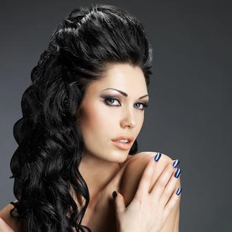 Portrait d'une belle femme brune avec une longue coiffure créative