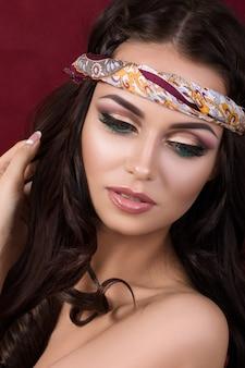 Portrait de la belle femme brune avec maquillage mode et foulard coloré sur la tête