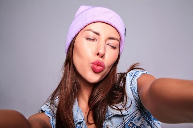 Portrait de la belle femme brune mignonne modèle dans des vêtements de jeans d'été décontractés sans maquillage en bonnet violet faisant photo selfie sur téléphone isolé sur gris. donner un baiser d'air