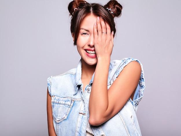 Portrait de la belle femme brune mignonne modèle dans des vêtements de jeans d'été décontractés sans maquillage avec une coiffure de cornes isolée sur fond gris. couvrant son visage avec la main