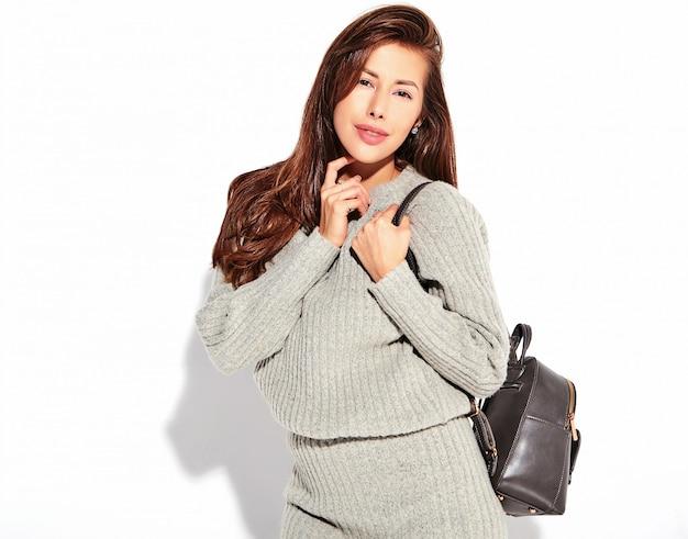 Portrait de la belle femme brune mignonne modèle dans des vêtements de sport gris automne décontracté sans maquillage isolé sur blanc avec sac à main