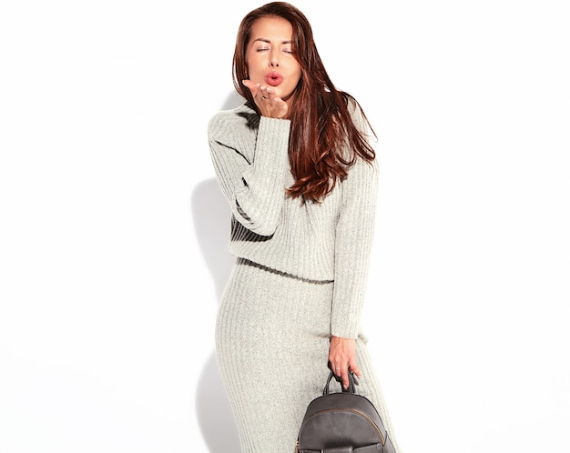 Portrait de la belle femme brune mignonne modèle en vêtements de sport gris automne décontracté sans maquillage isolé sur blanc avec sac à main. donner un baiser