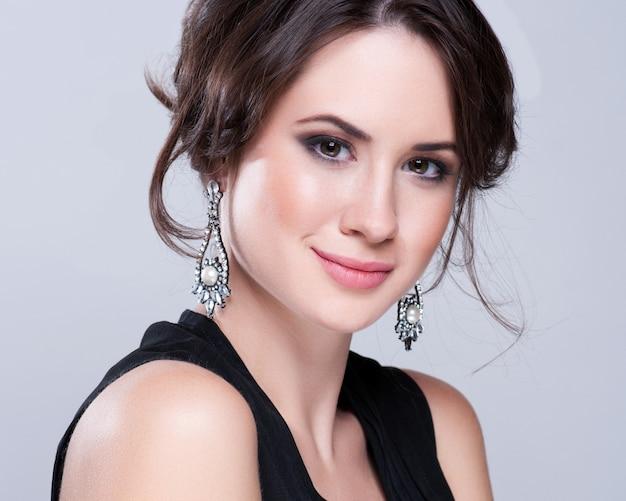 Portrait de belle femme brune en robe noire. ombres à paupières cosmétiques.