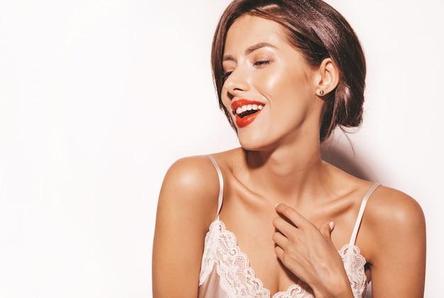 Portrait de la belle femme brune sensuelle. fille dans des vêtements classiques beiges élégants. modèle avec des lèvres rouges isolé sur blanc