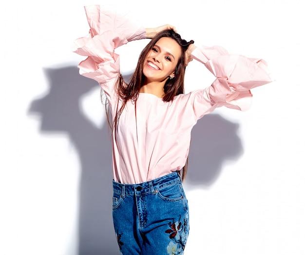 Portrait de la belle femme brune souriante caucasien modèle en chemisier rose vif et élégant jean bleu avec imprimé fleurs