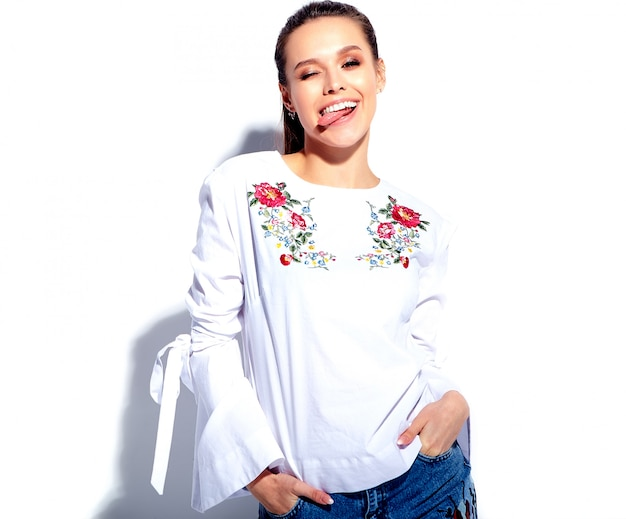 Portrait de la belle femme brune souriante caucasienne modèle en blouse blanche et élégant jeans bleu d'été avec des fleurs imprimer