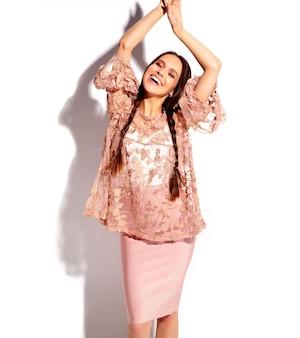 Portrait de la belle femme brune souriante caucasienne modèle avec double nattes en vêtements élégants d'été rose vif